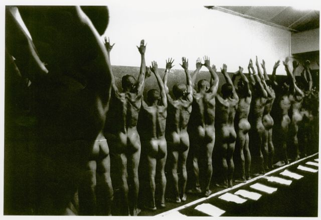 Mineworkers stripped naked and lined up for inspection. A Peter Magubane classic.