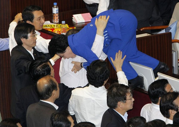 Lawmakers of opposition parties help their fellow lawmaker who tries to escape as they scuffle with lawmakers of GNP at National Assembly plenary session hall in Seoul